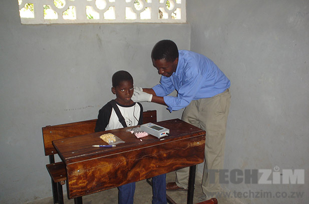 Tendekayi Katsiga working with a hearing impaired child.