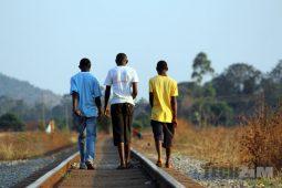 Young men walking along a railway line