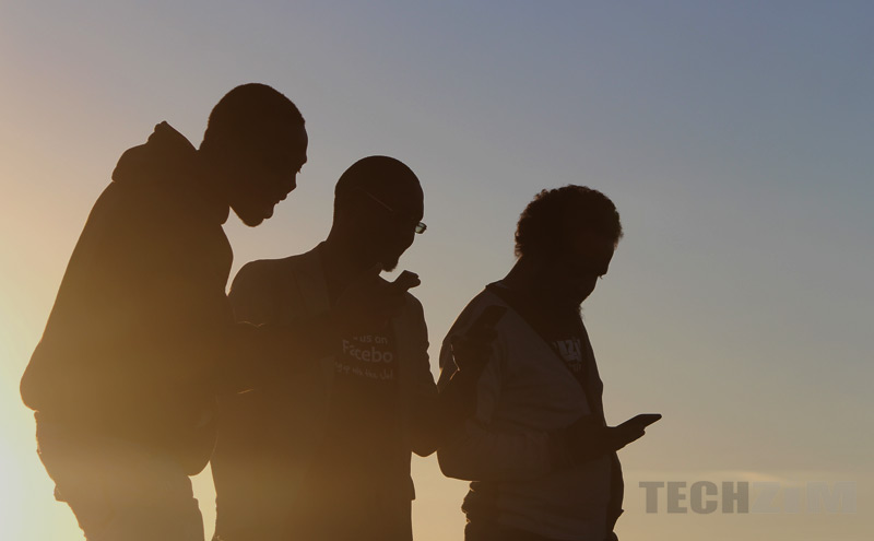 silhouette of men on mobile phones