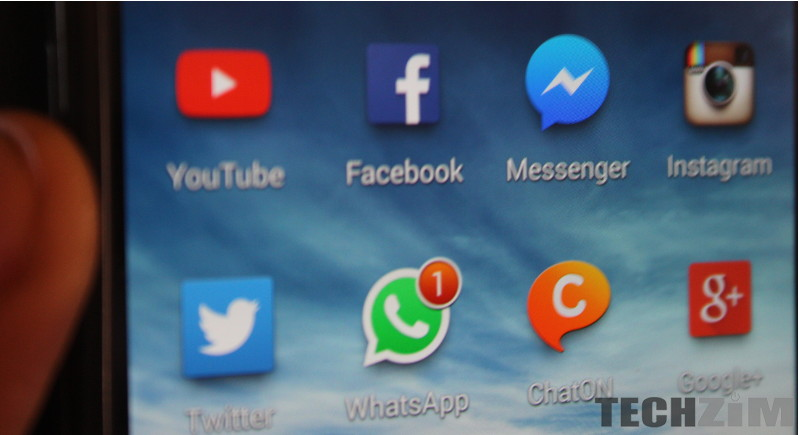 Phone screen showing various social media apps, WhatsApp included