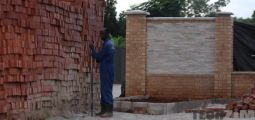 Builder next to bricks near a wall